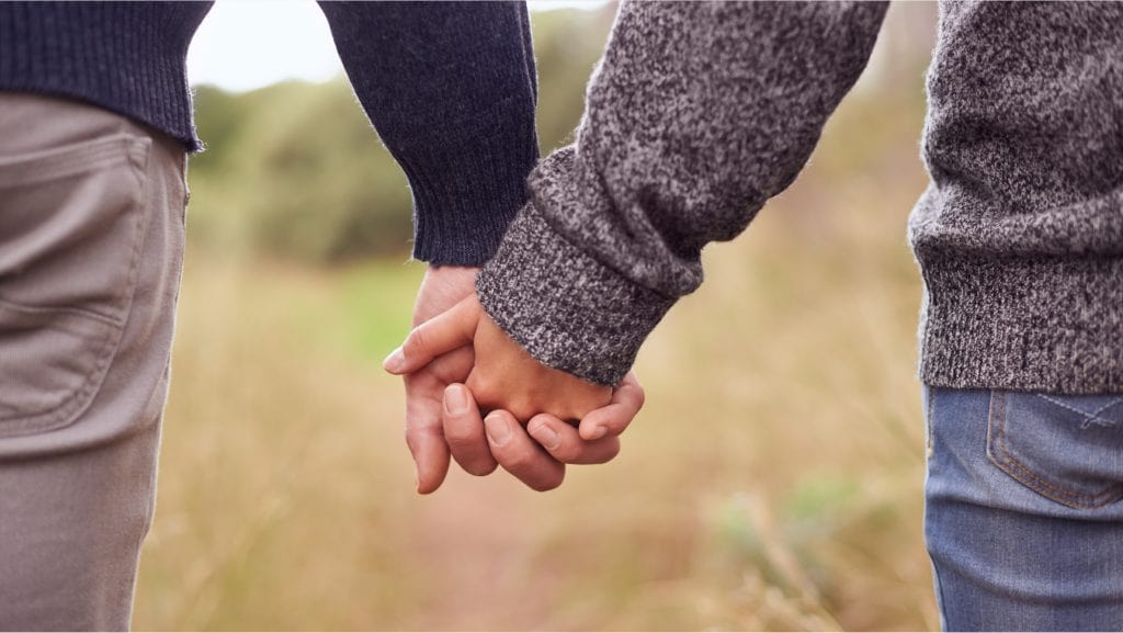 A couple holding hands together in the field
