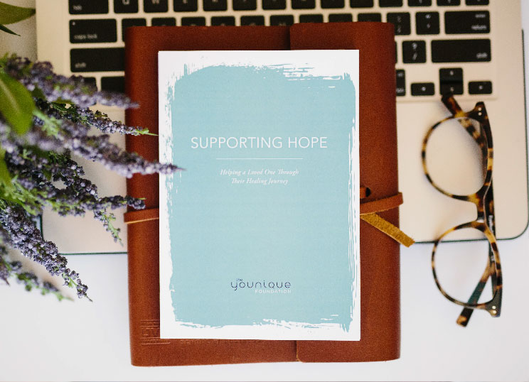 """A card with """"Supporting Hope"""", a notebook and a pair of glasses on the laptop"""