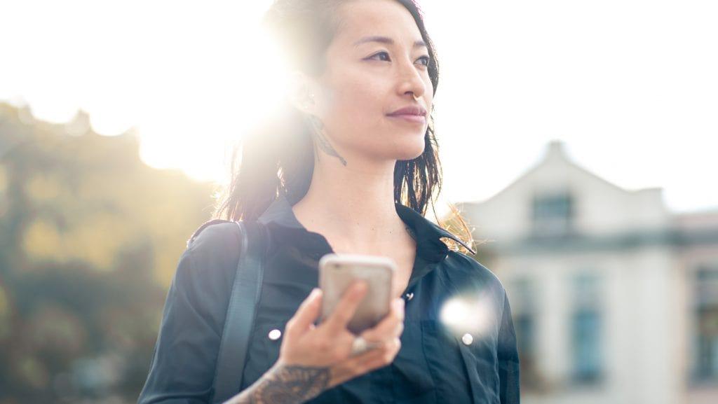 an asian woman holding a phone